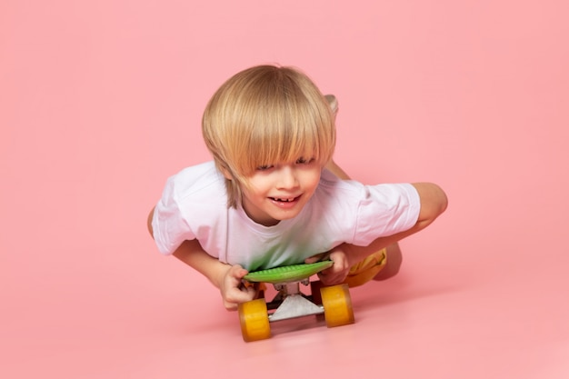 Вид спереди белокурый мальчик в белой футболке катается на скейтборде на розовом полу