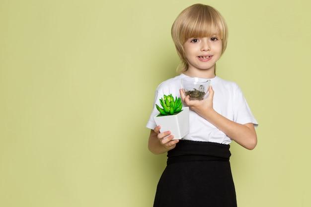 Вид спереди блондинка мальчик улыбается очаровательны, держа зеленый маленький завод в белой футболке на каменном столе coloerd