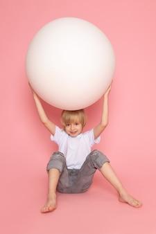 ピンクの机の上の丸い白いボールで遊ぶ白いtシャツで正面金髪のかわいい男の子