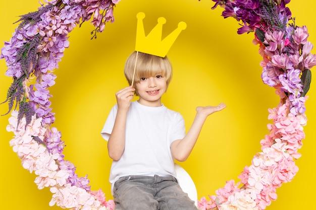 Вид спереди белокурый милый мальчик в белой футболке, улыбаясь, сидя на цветке сделал стойку на желтом столе