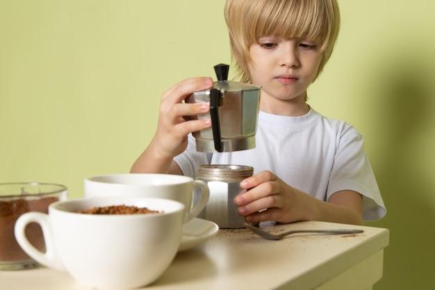 石色の机の上のテーブルでコーヒードリンクを準備する白いtシャツで正面金髪の子供