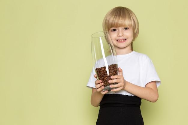 Вид спереди блондинка улыбается мальчик в белой футболке, держа бокал с коричневыми семенами кофе на каменном полу