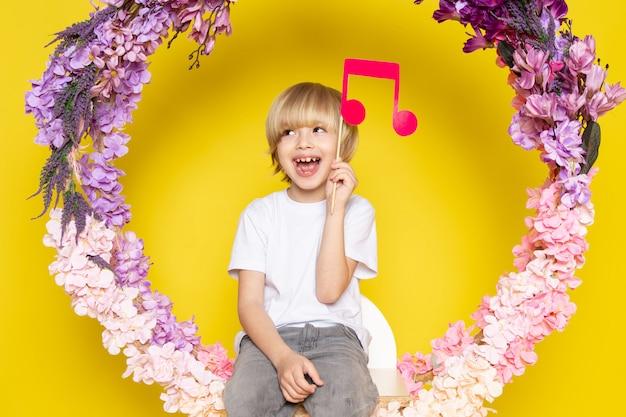 Вид спереди белокурого улыбающегося мальчика в белой футболке с розовой запиской на цветочной подставке на желтом столе