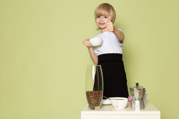 石色の床にコーヒーの飲み物を準備する白いtシャツで正面金髪笑顔少年