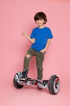 ピンクのスペースにセグウェイに乗っている青いtシャツとカーキ色のズボンを着た正面少年