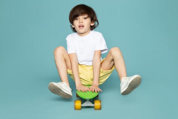 Мальчик спереди в белой футболке и желтых джинсах катается на зеленом скейтборде по синему пространству