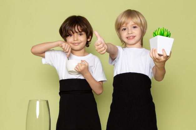 Вид спереди мальчики мило улыбаясь, держа зеленый маленький завод и кофе на каменном полу