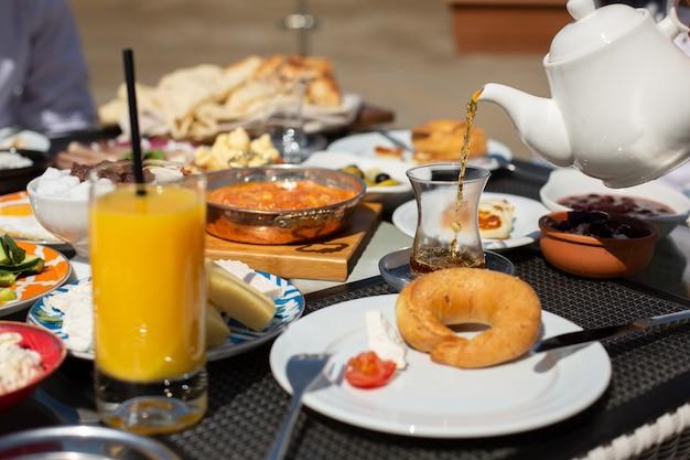 Стол для завтрака, вид спереди, люди вокруг стола, которые едят во время дневной еды, завтрака, чая