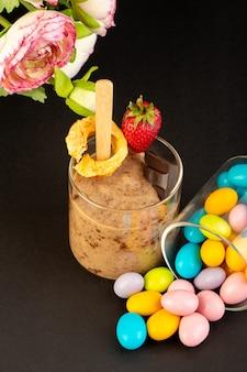 Вид спереди коричневый шоколадный десерт вкусный вкусный сладкий с порошкообразным кофе шоколадный батончик и клубника с конфетами на темном фоне сладкий освежающий десерт