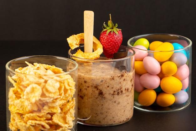 Вид спереди коричневый шоколадный десерт вкусный вкусный сладкий с порошковым кофе шоколадный батончик и клубника с кукурузными хлопьями и конфетами на темном фоне сладкий освежающий десерт