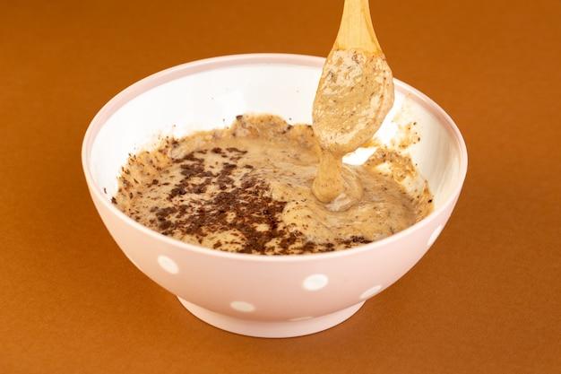 正面図茶色のチョコデザートおいしいおいしい甘いミルクコーヒーの背景に分離された白いプレート内の粉末コーヒーと甘い新鮮なデザート