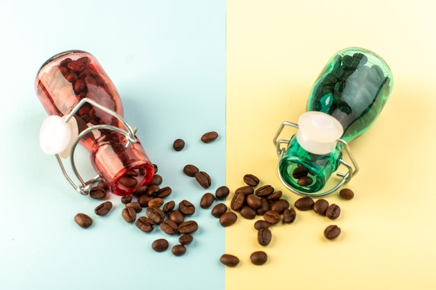 青黄色の表面の着色されたガラスの瓶の中の正面の茶色のコーヒー種子
