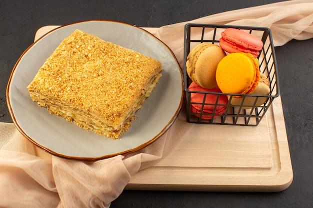 Кусочек торта, вид спереди с вкусными французскими макаронами, запеченными на внутренней тарелке на деревянном столе и темным сладким бисквитом