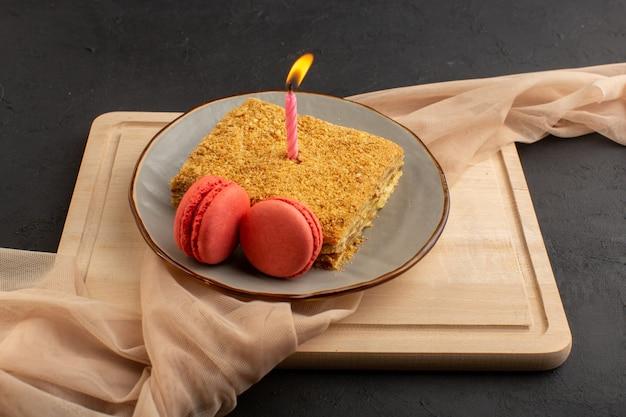 正面のケーキスライスおいしいと木製の机の上のろうそくとマカロンと暗いケーキビスケット砂糖でプレートの内側を焼いた