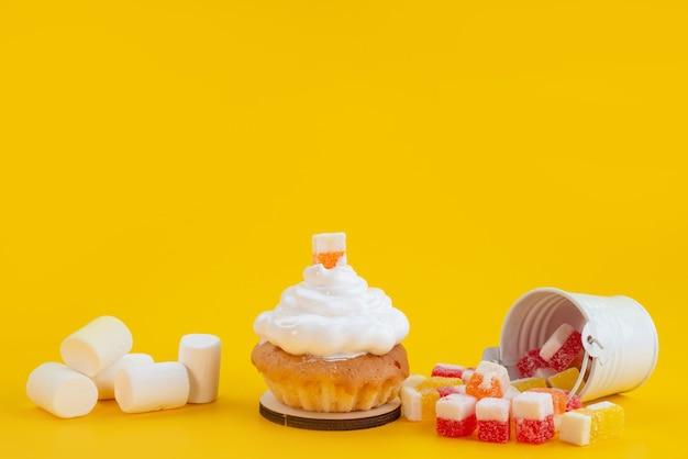Конфеты и зефир, вид спереди с маленьким пирогом на желтом, сладкий бисквитный торт