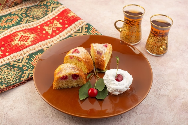 ピンクの机の上にクリームと正面から見たチェリーケーキのスライス