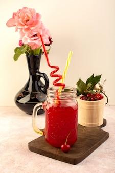 正面から見たチェリーカクテルレッド、ストローの入った小さな缶、木製の机の上で新鮮なさくらんぼと花とピンクのデスク