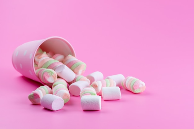 ピンク、甘い砂糖の色で甘くておいしいマシュマロを噛む正面図