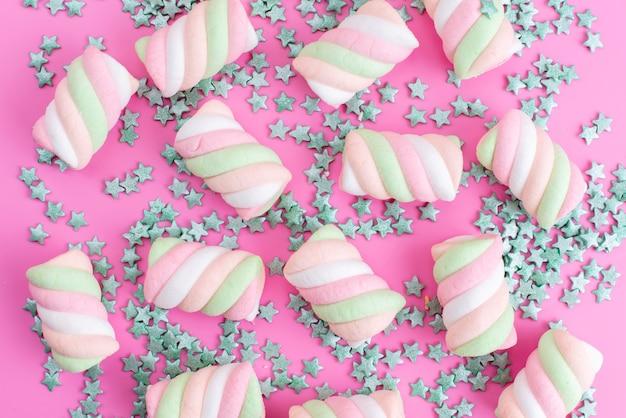 Жевательный зефир на розовом фоне, вид спереди, с частицами конфет в форме звезды, цветным радужным сахарным конфитюром
