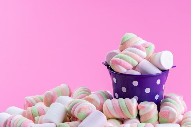 Вид спереди жевательного зефира в фиолетовой чашке и все на розовом, цветном радужном сахарном конфитюре