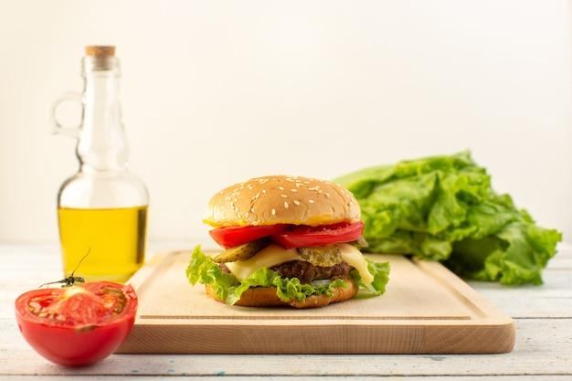 木製の机の上にオリーブオイルとサンドイッチとファーストフードの食事をサンドイッチし、チーズとグリーンサラダと正面から見たチキンバーガー