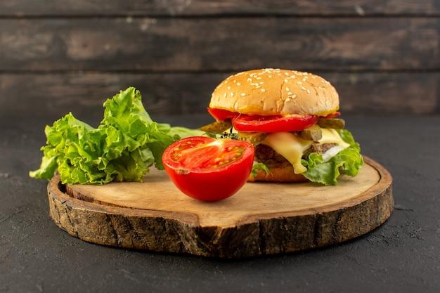 木製の机の上のトマトとサンドイッチ、ファーストフードの食事の食べ物とチーズとグリーンサラダの正面図チキンバーガー