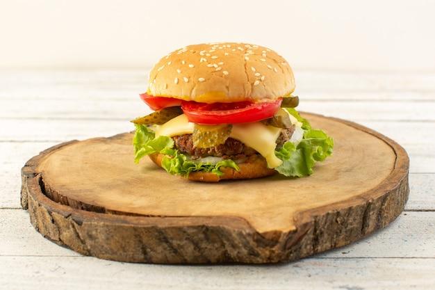 Куриный бургер с сыром и зеленым салатом на деревянном столе и бутерброд фаст-фуд, вид спереди