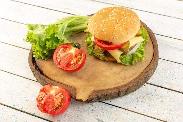 木製の机の上にチーズとグリーンサラダとサンドイッチファーストフードの食事と正面図チキンバーガー