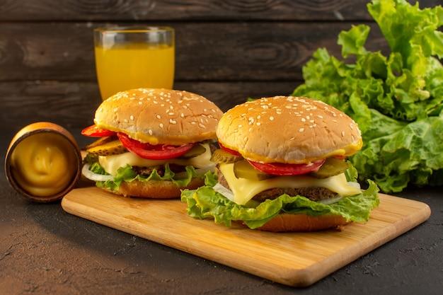 木製の机の上のチーズジュースとグリーンサラダとサンドイッチファーストフードの食事と正面図チキンバーガー