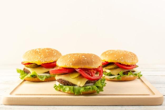 Куриные гамбургеры с сыром и зеленым салатом на деревянном столе и сэндвич-фаст-фуд, вид спереди