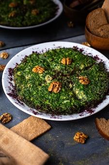 Салат с курицей спереди с грецкими орехами и зеленью внутри белой тарелки вместе с булочками с хлебцами на сером столе овощной салат майонез