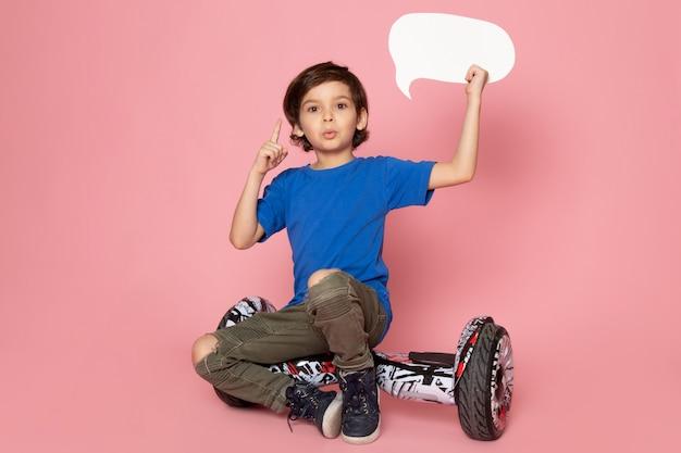 ピンクのスペースでセグウェイに座っている白い看板を持っている青いtシャツの正面の子少年