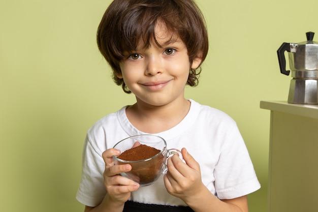 Ребенок спереди улыбающийся мальчик, обожаемый в белой футболке с порошкообразным кофе на каменном цветном пространстве