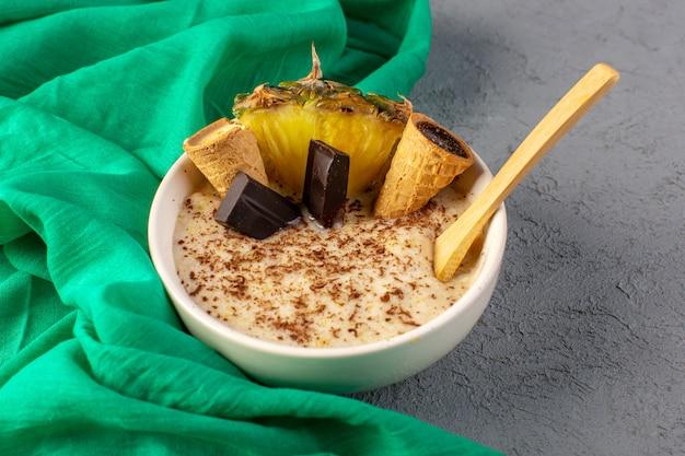 Шоколадный десерт спереди коричневого цвета с кусочками ананаса и шоколадными батончиками внутри белой тарелки вместе с зеленой салфеткой на сером