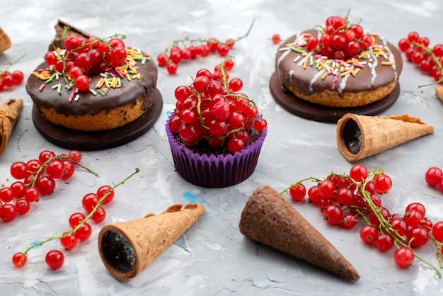 Вид спереди шоколадные торты с пончиками с фруктами и рогами на белом фоне торт, бисквит, пончик, шоколад