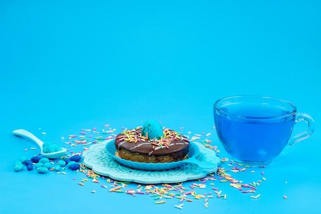 Вид спереди шоколадный пончик вместе с синим, напиток на синем, сладкие конфеты