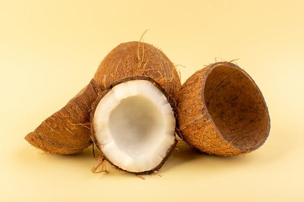 正面のココナッツクリーム色の背景に分離された乳白色の新鮮なまろやかなトロピカルエキゾチックなフルーツナッツをスライス