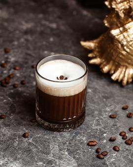 灰色の机の上の氷とコーヒーの種子と正面図のコーヒーカクテルジュースカクテルを飲む