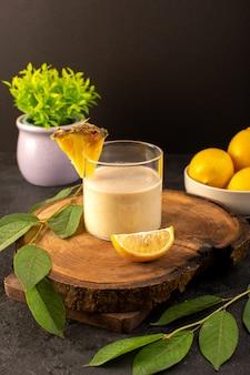 Вид спереди холодный коктейль, окрашенный внутри стекла с зелеными листьями и лимонами, маленькое растение, изолированное на темноте