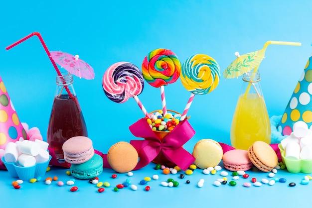 Вид спереди цветных коктейлей, охлаждающихся вместе с леденцами на французских макаронах и разноцветными конфетами на синем фоне.