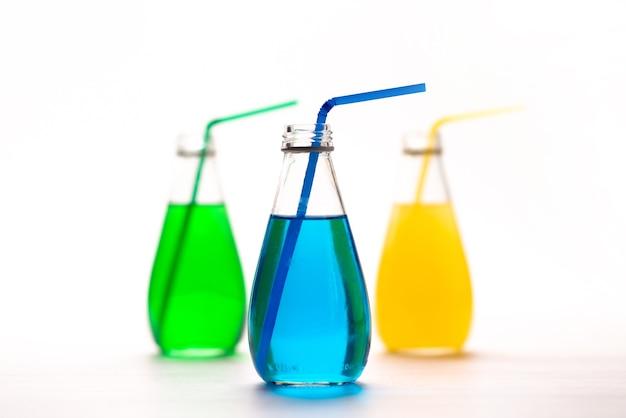 Вид спереди цветные напитки с соломинкой внутри бутылок на белом, цвет напитка сока