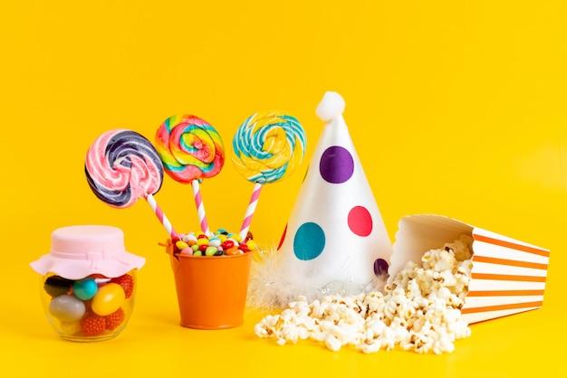 Вид спереди цветные леденцы на палочке с разноцветными конфетами, забавная шапочка и попкорн на желтом