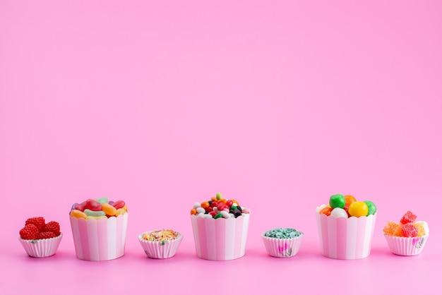 Вид спереди красочные конфеты внутри бумажных пакетов на розовом, цветном сладком сахаре