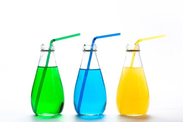 Вид спереди красочные коктейли с соломкой на белом, цвет напитка сока