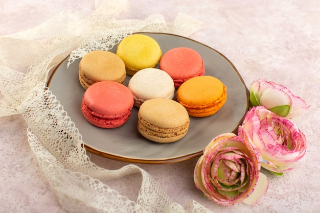 ピンクの机の上の皿の中にバラと正面のカラフルなフランスのマカロン