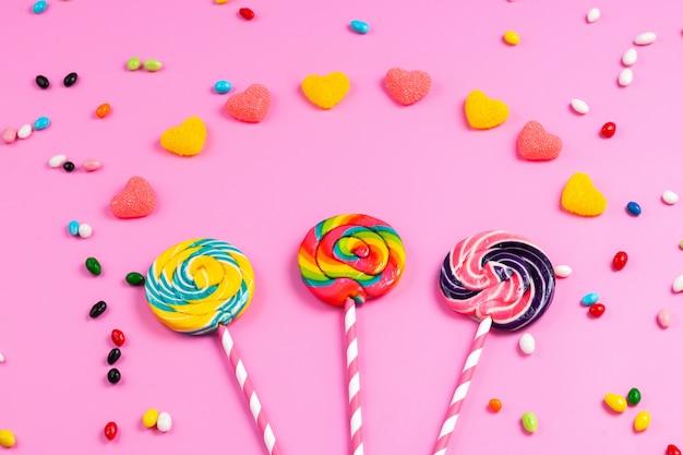 Вид спереди, красочные леденцы на палочке на розово-белых сладких соломенных палочках, мармелад в форме сердца и разноцветные конфеты на розовом
