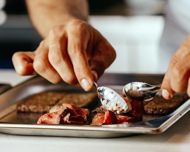 Повар, вид спереди, готовит мясное покрытие внутри тарелки, жарит мясную пищу