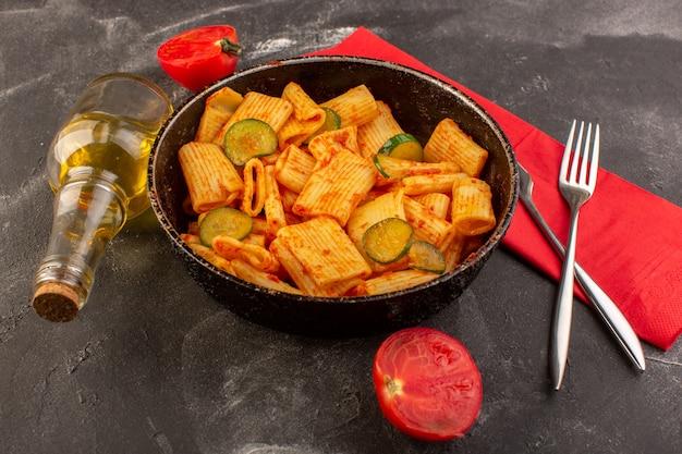 Вид спереди приготовленная итальянская паста с томатным соусом и огурцом внутри сковороды на темном столе