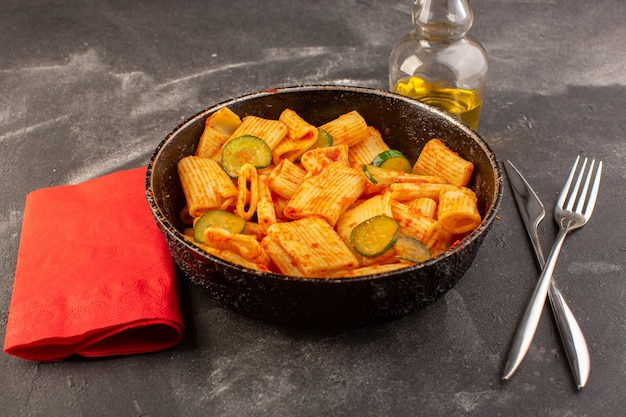 正面は、暗い表面に鍋にトマトソースとキュウリのイタリアンパスタを調理