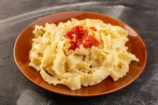 Вид спереди приготовленные итальянские макароны с томатным соусом внутри тарелки на серой поверхности